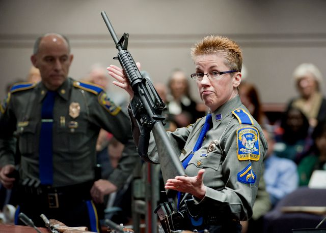 FILE - In this Jan. 28, 2013, file photo, firearms training unit Detective Barbara J. Mattson, of the Connecticut State Police, holds up a Bushmaster AR-15 rifle, the same make and model of gun used by Adam Lanza in the Sandy Hook School shooting, during a hearing of a legislative subcommittee in Hartford, Conn. Remington, the gunmaker beset by falling sales and lawsuits tied to the Sandy Hook Elementary School massacre, said Monday, Feb. 12, 2018, that it has reached a financing deal that would allow it to continue operating as it files for Chapter 11 bankruptcy protection. (AP Photo/Jessica Hill, File)