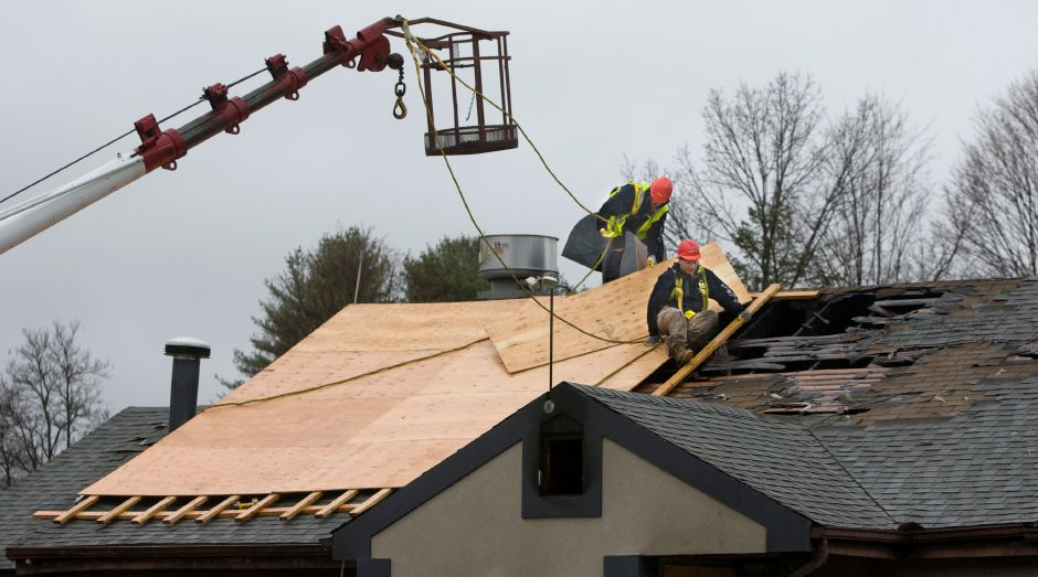 Crews work to patch the roof after an early-morning blaze heavily damaged about half of Renaldo's Pizza on North Main Street in Southington, Thursday, April 7, 2016. | Dave Zajac/Record-Journal