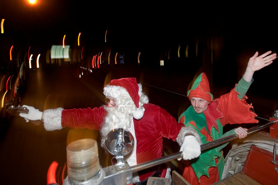 Santa Clause played by Bob Maloney from the Wallingford VFW waves to children from the back of a Plantsville Firehouse Emergency Vehicle to children along West Main Street in Plantsville with an elf played by Chris Levesque during the Christmas in the Village of Plantsville, Thursday, November 2, 2010. (Johnathon Henninger/ Record-Journal)