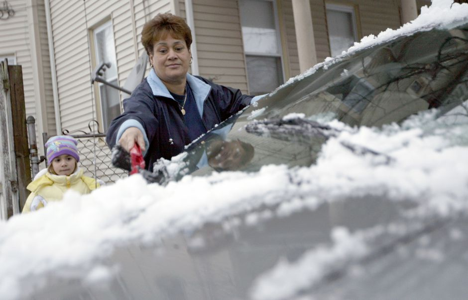 MERIDEN, Connecticut - Wednesiday, December 9, 2009 - Meriden resident Gloria Cordero removes snow off her car as her granddaughter Anahya Ellen, 4, watches on Wednesday afternoon, December 9. Rob Beecher / Record-Journal