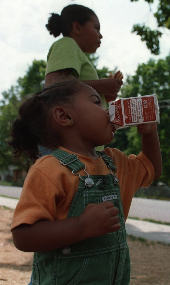Azeala Harkless pours down a carton of milk at the daily Community Action Agency of Meriden free lunch at Britannia Park July 29, 1999. She