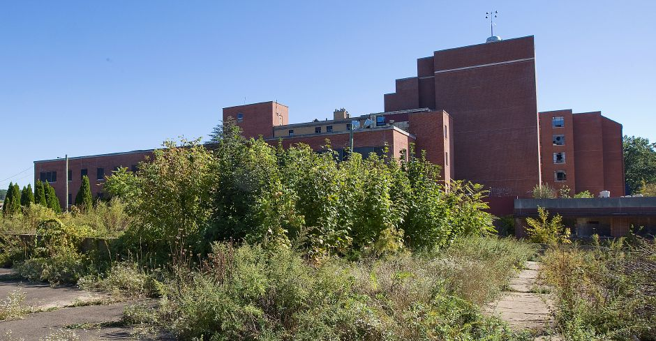Plant growth overtakes the rear parking lot of the former Meriden-Wallingford Hospital in Meriden, Thursday, October 6, 2016. | Dave Zajac, Record-Journal