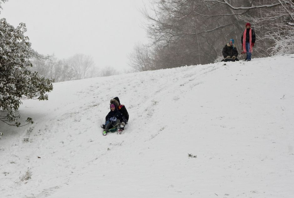 Gina Maiorano, 13, of Meriden, and Stephanie Michaud, 14, of Wallingford, sled down a hill in Walnut Grove Cemetery while their friends Brittany Fuchs, 15, and Zak Belanger, 15, both of Meriden, top right, watch in Meriden, Wednesday afternoon, Feb. 10, 2010. There was just enough snow on the ground for the teens to get a few runs down the hill in around around 4:30 p.m. during the snow storm. (Christopher Zajac/Record-Journal)