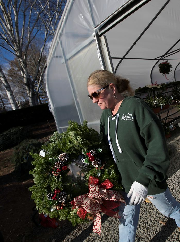 Alison Kogut, office manager, carries a Christmas wreath for a customer at Kogut