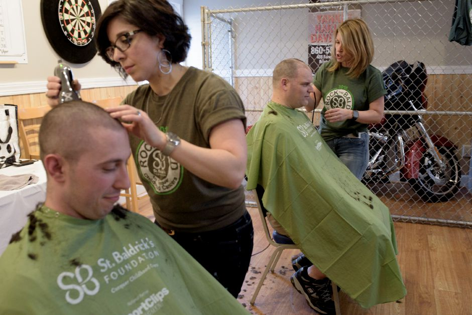 Matt Ackerman and Dan Spetland of North Haven Fire shave their heads during the St. Baldrick
