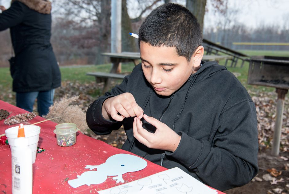 Christian Montalvo, 11, of Meriden, decorates a snowman at the Holiday Celebration on the Linear Trail at Lakeside Park in Wallingford Sunday. The event was organized by the Linear Trail Advisory Committee, which helps maintain the trail.
