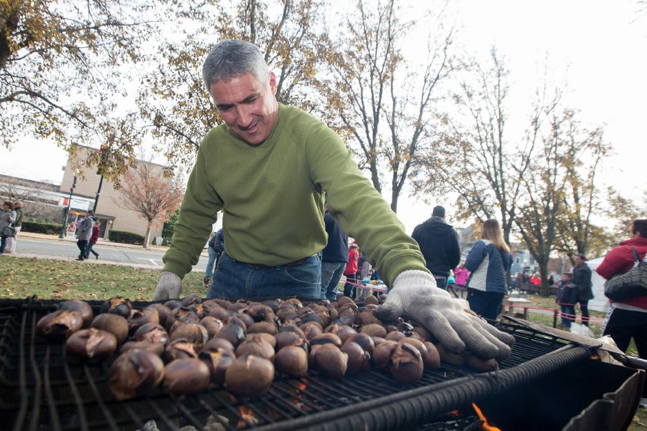 Mickey Wells turns chestnuts on the grill Saturday during Season of Celebration at the Town Hall in Wallingford December 2, 2017 | Justin Weekes / For the Record-Journal