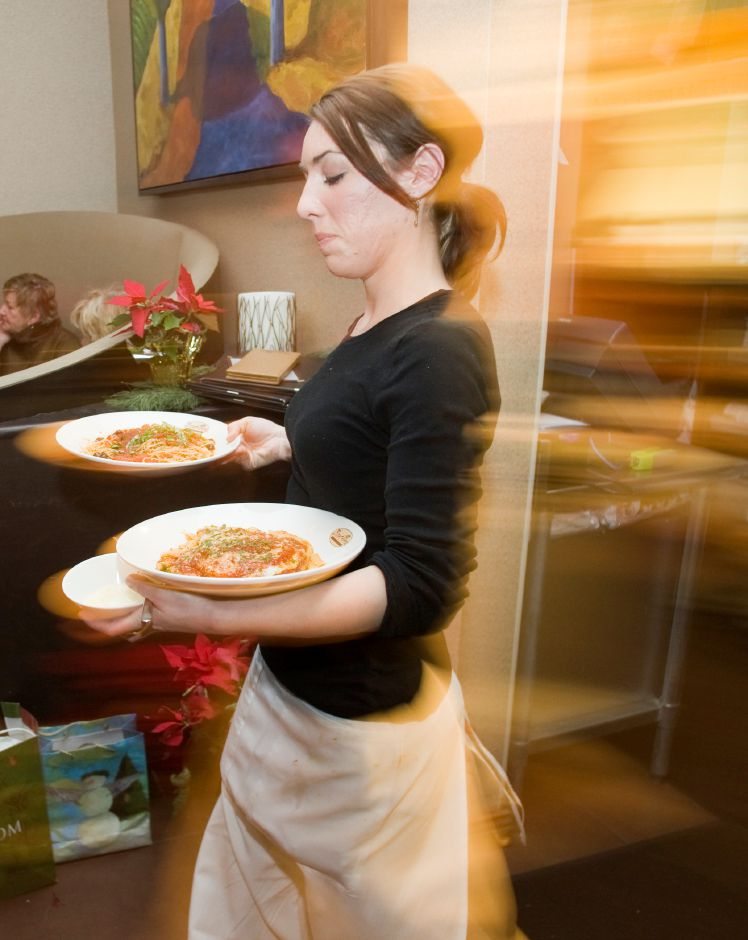 "A waitress leaves the kitchen with two entrees for customers at Bonterra in Southington, Tuesday night, Weds. 23, 2008. Many people were repeat customers participating in the ""Midweek Madness"" special. (Christopher Zajac/Record-Journal)"