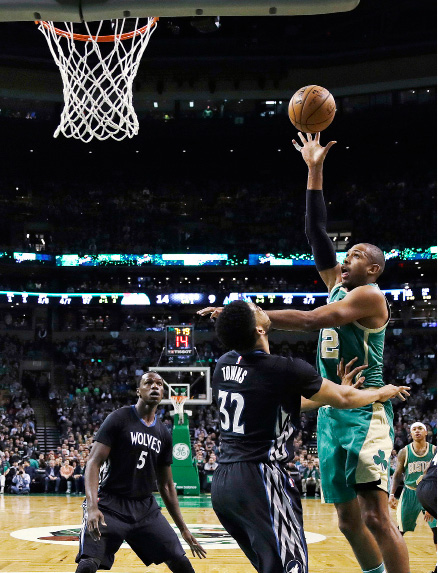 Boston Celtics center Al Horford, right, shoots while covered by Minnesota Timberwolves center Karl-Anthony Towns (32) and forward Gorgui Dieng (5) during the first quarter of an NBA game in Boston, Wednesday, March 15, 2017. (AP Photo/Charles Krupa)