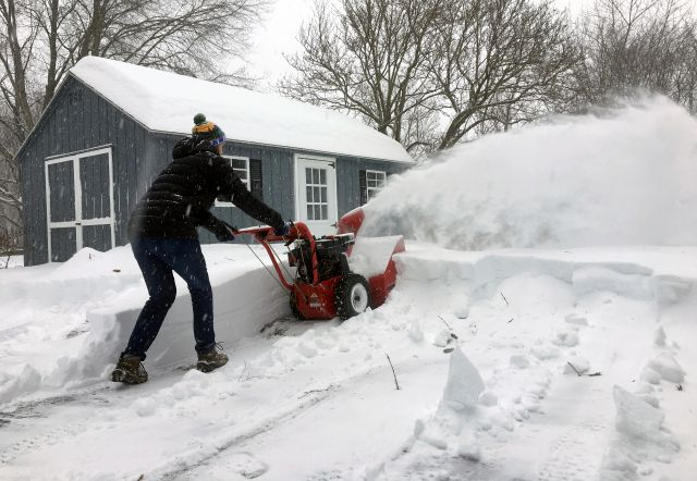 Ben Jennings snowblows his driveway on Sunday, Jan. 20, in Glenville, N.Y., where 16 inches of snow fell from Saturday evening through noon Sunday. (AP Photo/Mary Esch)