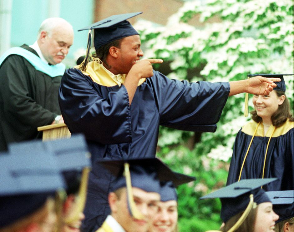 Robert Anthony Grace, Jr. gestures to the crowd as he walks up to receive his diploma at Platt High School graduation Thurs., June 15. On the left is school principal Timothy Gaffney.