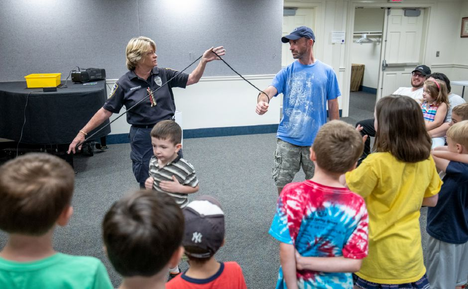 Plainville Animal Control Officer Donna Weinhofer demonstrates one of the tools she uses to handle animals. Weinhofer visited the Plainville Public Library Tuesday night to help families understand the animals which live around them. | Devin Leith-Yessian / Plainville Citizen