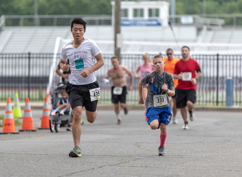 Lian-Wei Yuan, left, and Owen Richardson turn onto Robert Holcomb Way during the Chips Family Restaurant Road Race on July 21, 2019. Plainville residents along the race