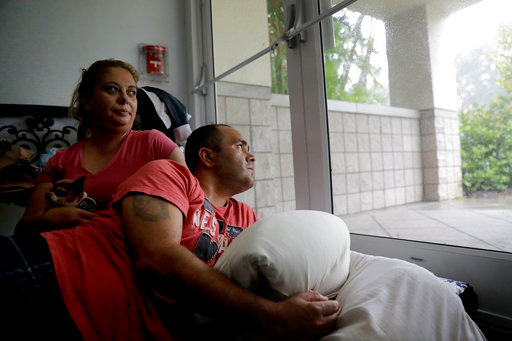 Javier Garcia, right, and his wife Marissa Soto sit with their neighbor