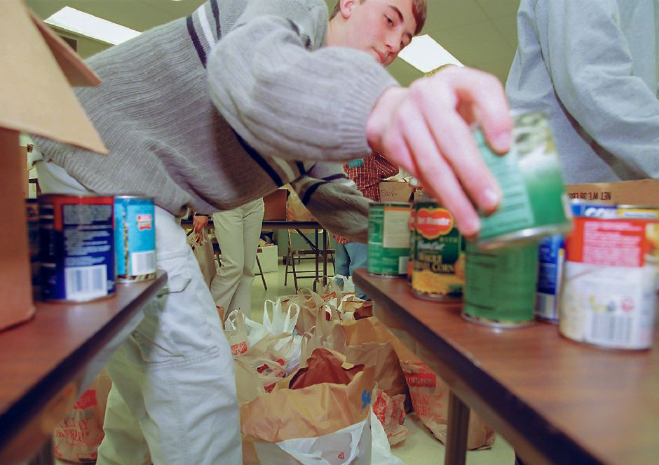 RJ file photo - Ryan Puzycki, a member of the student council at Lyman Hall High School in Wallingford, sorts cans of food with the other council members after school Dec. 1, 1998. The cans represent a small portion of the 2,850 nonperishable foot items the school collected for the Wallingford Holiday for Giving.