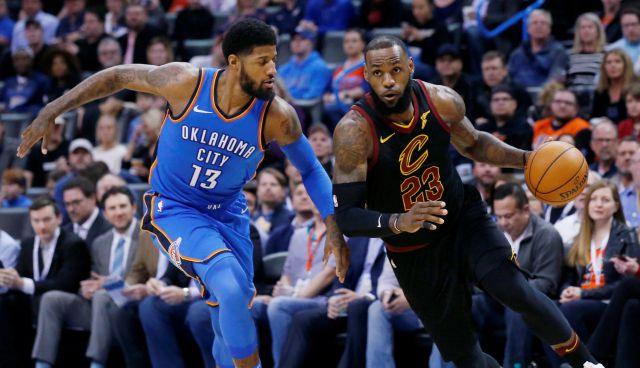 Cleveland Cavaliers forward LeBron James (23) drives past Oklahoma City Thunder forward Paul George (13) during the first half of an NBA basketball game in Oklahoma City, Tuesday, Feb. 13, 2018. (AP Photo/Sue Ogrocki)
