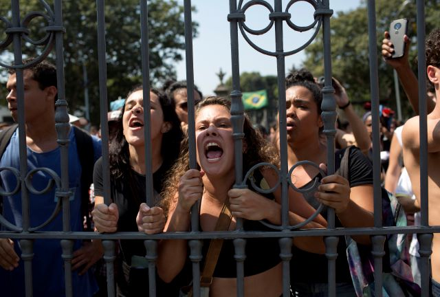 Students and National Museum employees protest outside the institution after it was gutted by an overnight fire in Rio de Janeiro, Brazil, Monday, Sept. 3, 2018. Recriminations flew over who was responsible for the loss of at least part of Latin America's largest archive of historical artifacts, objects and documents. (AP Photo/Silvia Izquierdo)