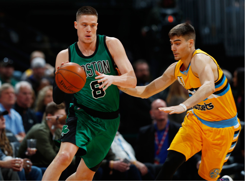 Boston Celtics forward Jonas Jerebko, left, of Sweden, fields a pass as Denver Nuggets forward Juancho Hernangomez, of Spain, defends in the first half of an NBA basketball game Friday, March 10, 2017, in Denver. (AP Photo/David Zalubowski)