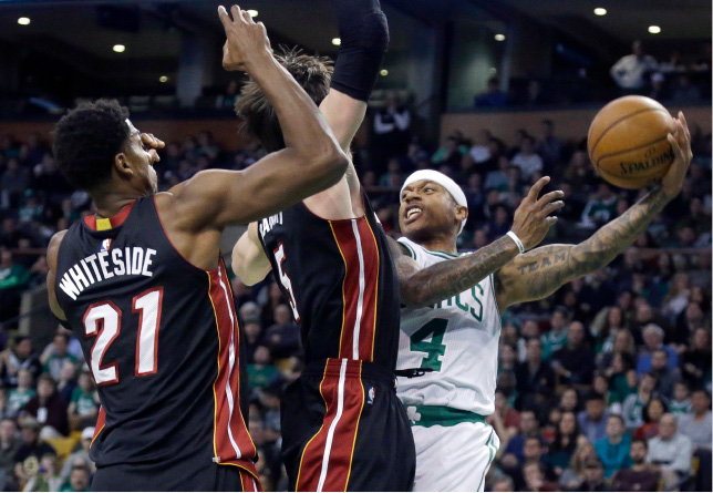 Boston Celtics guard Isaiah Thomas (4) passes the ball against the defense of Miami Heat forward Luke Babbitt (5) and center Hassan Whiteside (21) in the first quarter of an NBA basketball game, Friday, Dec. 30, 2016, in Boston. (AP Photo/Elise Amendola)