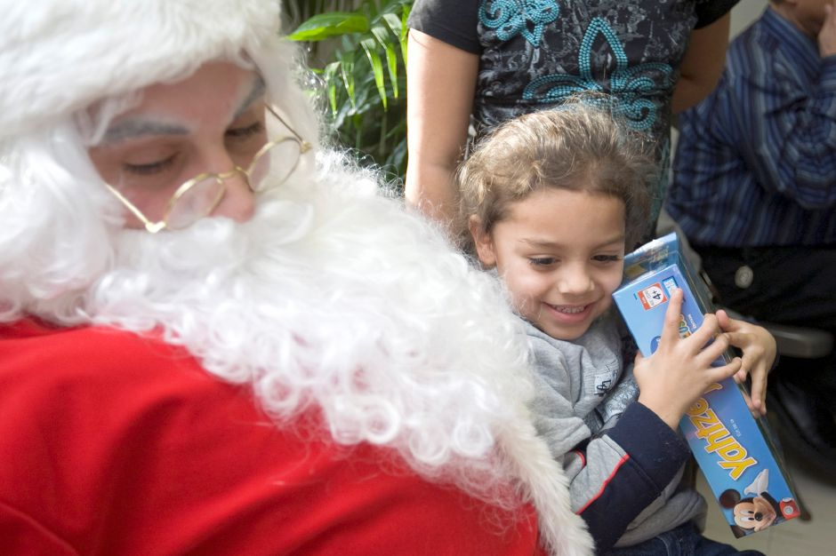Favian Motes, 4, happily squeezes the Yahtzee game just given to her by Ron Maringola, dressed as Santa at the Hispanos Unidos Christmas Party at Casa Boricua in Meriden on Thursday, December 16, 2010. Favian Motes was there with her sister, Laysha montes, 9, and brother, Angel Montes, 6, mother, Vilmarie Gonzalez and Father, Victor Pedraza. The family lives in New Britain. Donations from Advanced Spinal Care, Thug Riders, Dog Pound Riders of Middletown and Lido