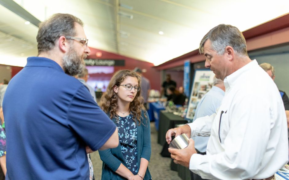 Audrey Larson, 15, watches Don Cornwall, vice president of APS Technology, demonstrate a part made by the company. Aside from listening to speakers and play math games, children were able to speak with local manufacturers during the Wallingford School