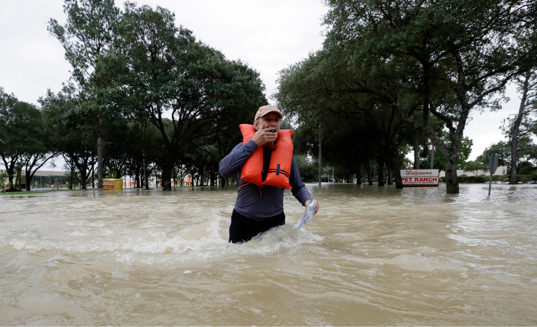 Mike Bialka holds a cigar as he makes his way through floodwaters from Tropical Storm Harvey to help a friend secure his home Wednesday, Aug. 30, 2017, in Kingwood, Texas. (AP Photo/Gregory Bull)
