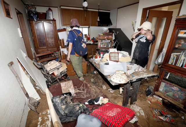 Residents return to their house and look at the damage after heavy rain hit southwestern Japan, in Kure, Hiroshima prefecture, Monday, July 9, 2018. Rescuers in southwestern Japan dug up more bodies Monday as they searched for dozens still missing after heavy rains caused severe flooding and left residents to return to their homes unsure where to start the cleanup. (Kyodo News via AP)