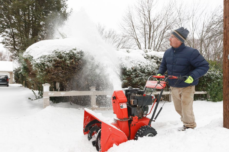 Patrick Patterson of Wallingford watches as his snow blower sends snow over the bushes in front of his house after the snow storm Sunday in Wallingford December,15 2013 | Justin Weekes / For the Record-Journal