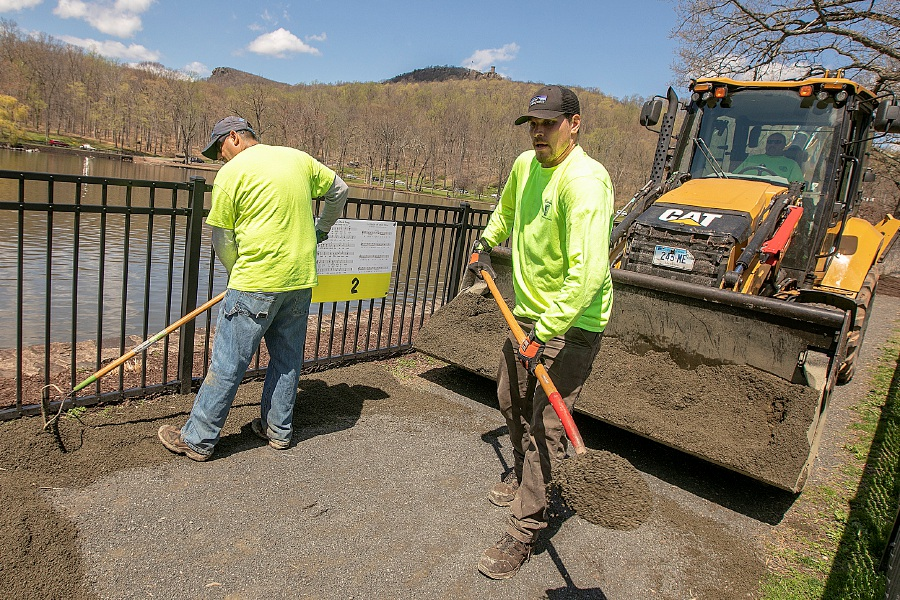 Parks and Recreation workers Sal DiDomenico, left, and Joe Winoski spread screenings on a path along Mirror Lake Tuesday in preparation for the annual Daffodil Festival at Hubbard Park in Meriden. Photos by Dave Zajac, Record-Journal
