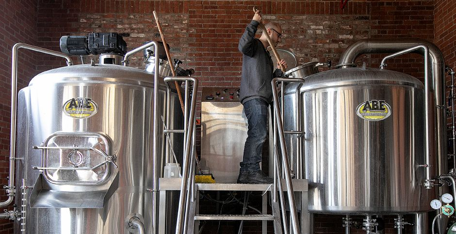 "Josh Norris, owner of Witchdoctor Brewing Company, stirs his newest brew ""Wholy Water,"" at the business on Thursday. Police say thefts at the brewery and St. Paul's Episcopal Church could be connected.Photos by Dave Zajac, Record-Journal"