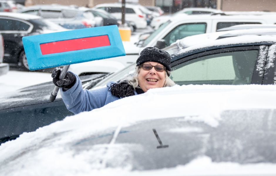 Joanne Gayeski, of Middletown, clears snow off her car during Saturday