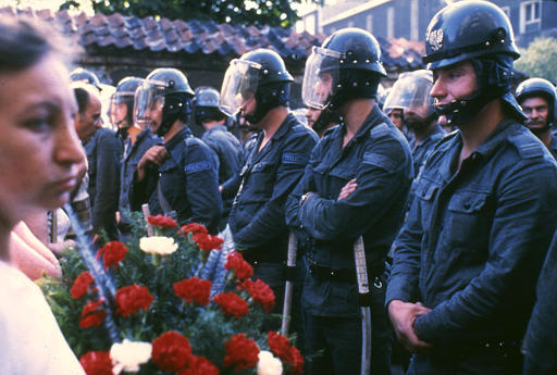 Polish police officers oppose protestors with flowers who came to follow Lech Walesa