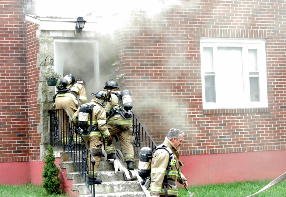 Record Journal Photo/ Johnathon Henninger 9.05.08 - Firemen enter the home at 30 Lincoln Terrace in Meriden after a neighbor instructed a friend to call the police as she banged on the door to make sure no one was inside. A electrical fire started in the basement was suspected as the cause within minutes of the home being entered.