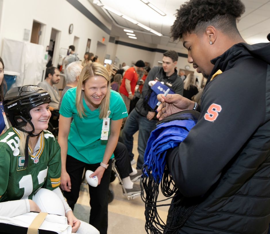 Andre Cisco signs an autograph for patient Carissa Walberg, of Southbury, left, next to Occupational Therapist Katie Zimmerli.