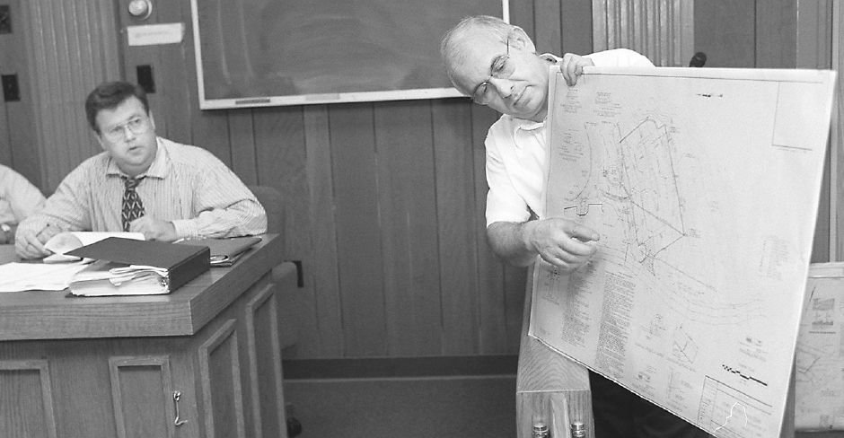 RJ file photo - Severino Bovino, land planner at Kratzert Jones & Associates Inc. of Southington, points out the area of a proposed boat launching ramp and parking lot for Crescent Lake at a Planning and Zoning Commission meeting Sept. 1, 1998. Town Planner Robert Nerny is seated at left.