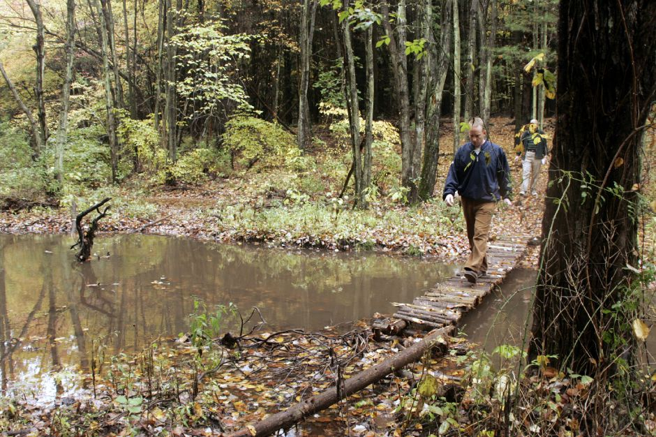 Michael Riccio, of the Open Space Committee, crosses a section of Patton Brook through the former Novick Orchard property that the Town of Southington purchased, Thurs., Oct. 12.