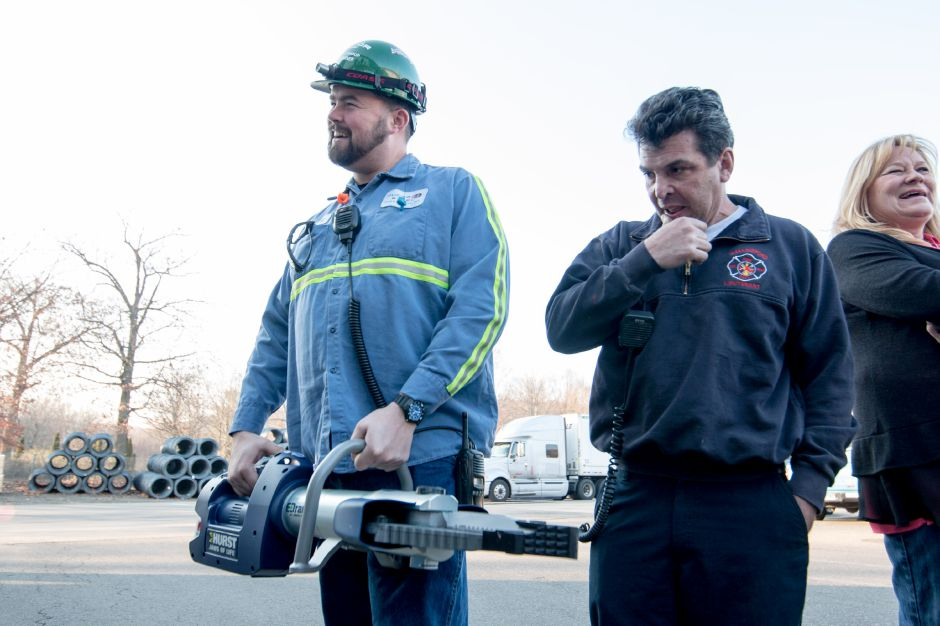 David Garner, a safety supervisor at Nucor Steel in Wallingford, holds the Jaws of Life tool the company gave to the Wallingford Fire Department on Monday. Nucor held a golf tournament in September to raise money for the tool and to donate to local charities. Devin Leith-Yessian | Record-Journal