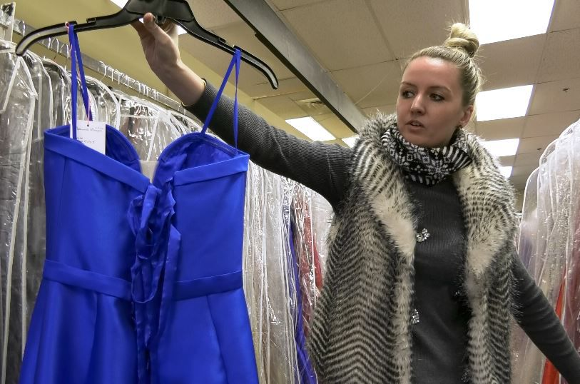 Owner Kristen Langan-Gudaitis holds up a prom dress with a lace-up back, a popular style, at Dynamite Designs by Kristen, 1157 N. Colony Rd. |Ashley Kus, Record-Journal