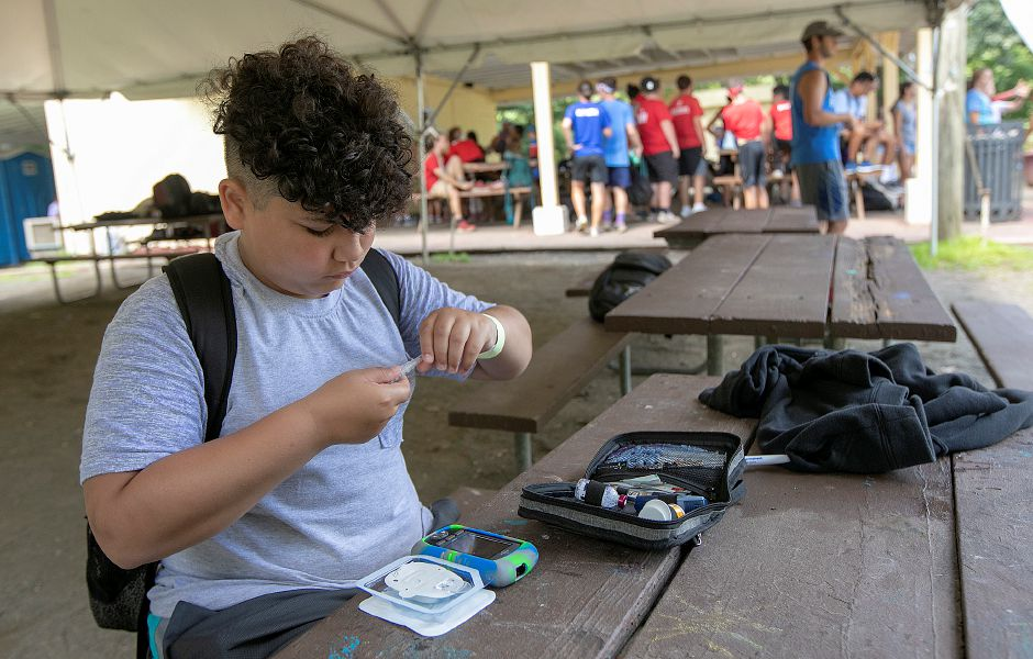 Javier Quiros, 12, of New Britain, sets up an insulin delivery pump before heading off to the next activity during a pilot diabetes day camp at the YMCA's Mountain Mist Outdoor Center in Meriden, Thurs., Aug. 8, 2019. The camp is run in conjunction with the Children's Medical Center in Hartford, the Y, and funded through the Lion's Club. Dave Zajac, Record-Journal