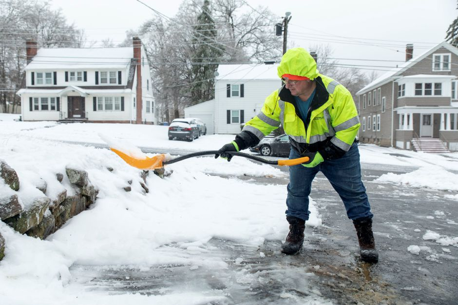 At left, Frank Companik, of Meriden, clears snow from his driveway after the snow stopped falling on Sunday. The storm delivered between 2.5 and 3.8 inches to the area, causing outages throughout the region. | Devin Leith-Yessian/Record-Journal