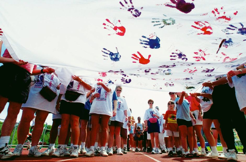 Participants in the Relay For Life move a cancer survivor banner hand to hand down Platt High School