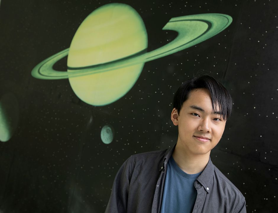 Choate Rosemary Hall junior HP Park, 17, stands next to a space mural in the Carl C. Icahn Center for Science, Thurs., Sept. 19, 2019. Park is a semifinalist in an international science contest. Dave Zajac, Record-Journal