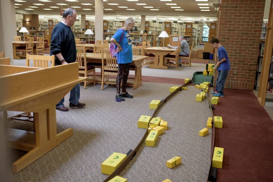 Wallingford residents Thirl and Debbie Gravell play the course with their grandson Vito Raso, 9, of Meriden. The Wallingford Public Library set up a mini-golf course on Saturday for ages 5+. Proceeds would benefit the library. Monica Jorge/Special to the Record-Journal