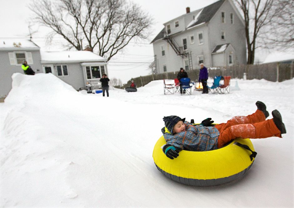 Jackson Marshall, 6, of Meriden, slides down a snow chute built by father, Todd, in the backyard of their residence on S. Broad St. in Meriden, Monday, February 9, 2015. | Dave Zajac / Record-Journal