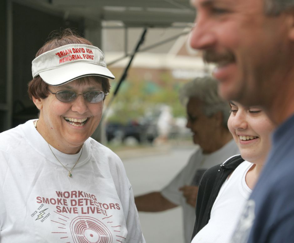 Roberta Ash, left, speaks with Meriden fire fighter Joe Erff, right, and her daughter Elizabeth Ash, center, in front of the Super Stop and Shop on East Main Street in Meriden Friday morning. This is the 19th annual Brian David Ash Memorial Fire Prevention Fundraiser. It will run from 10am to 8pm Friday, Saturday, and Sunday. They take donations and sell hotdogs to raise money for fire prevention. Brian David Ash is her late son who died in a fire. Chris Angileri.