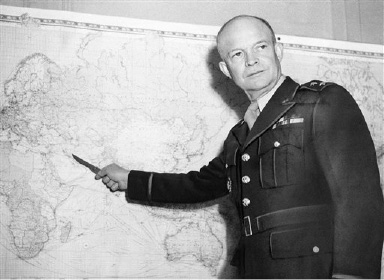 For a visitor to his London Headquarters Lt. Gen. Dwight D. Eisenhower in command of U.S. Army forces in the European War Theater, illustrates a point with one of the maps covering the office walls  July 17, 1942. (AP Photo)