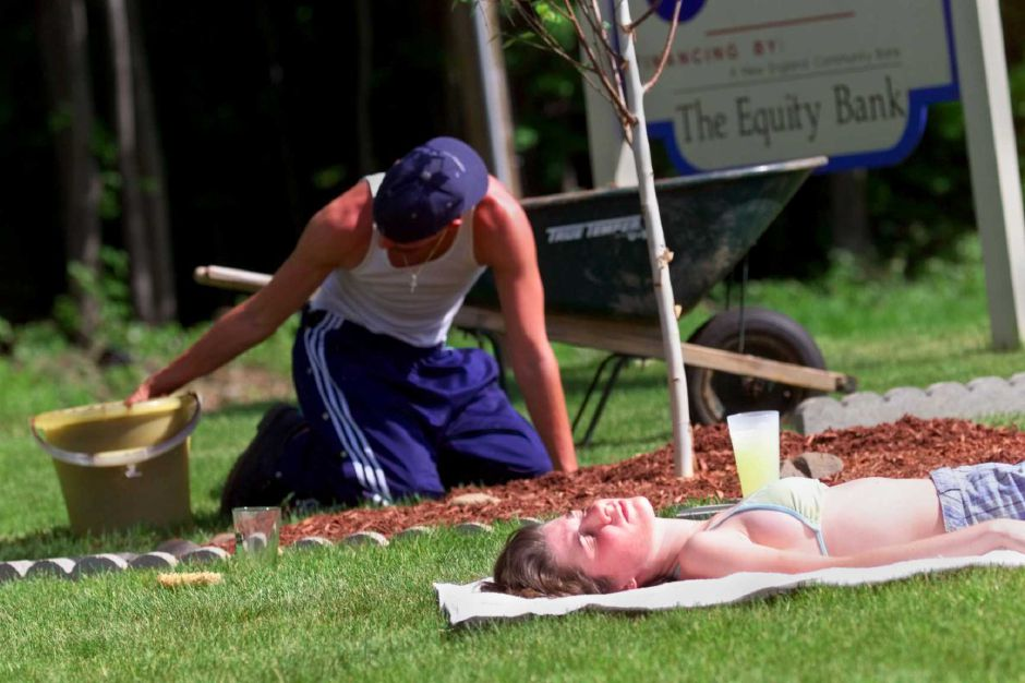 RJ file photo - Nicholas Lanigan does a little landscaping while his girlfriend, Jessica Luponio, basks in the afternoon sun outside his parent