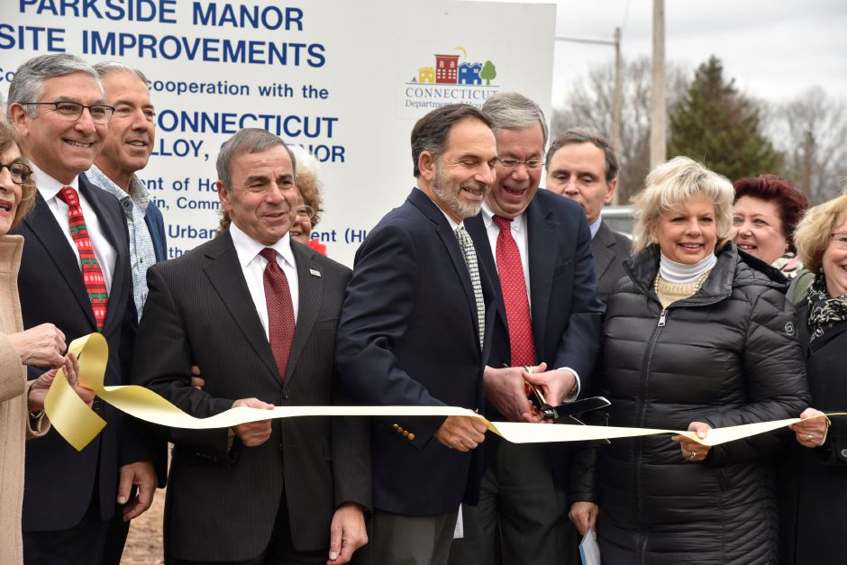Chairman of the Economic Development Commission of North Haven Richard LoPresti (center, with scissors) cuts a ceremonial ribbon during a dedication commemorating recent site improvements made at Parkside Manor, 191 Pool Rd., on Monday, Dec. 17. 2018. | Bailey Wright, Record-Journal