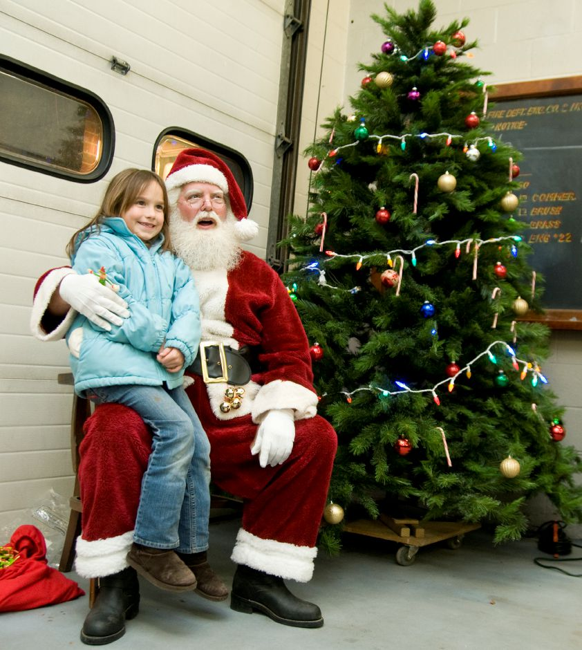 Southington resident Kristina Ferreri,7, smiles for the cameras as she sits on Santa