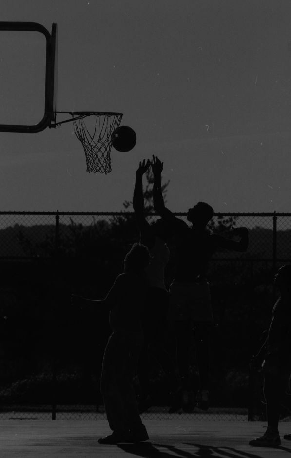 The evening sun silhouettes a group of basketball players during a game at Ceppa Field, July 1989.